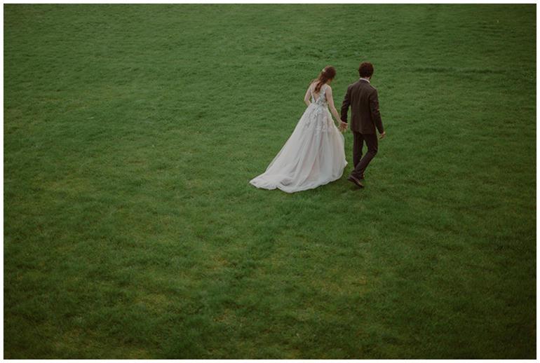 bride-groom-walking-grass